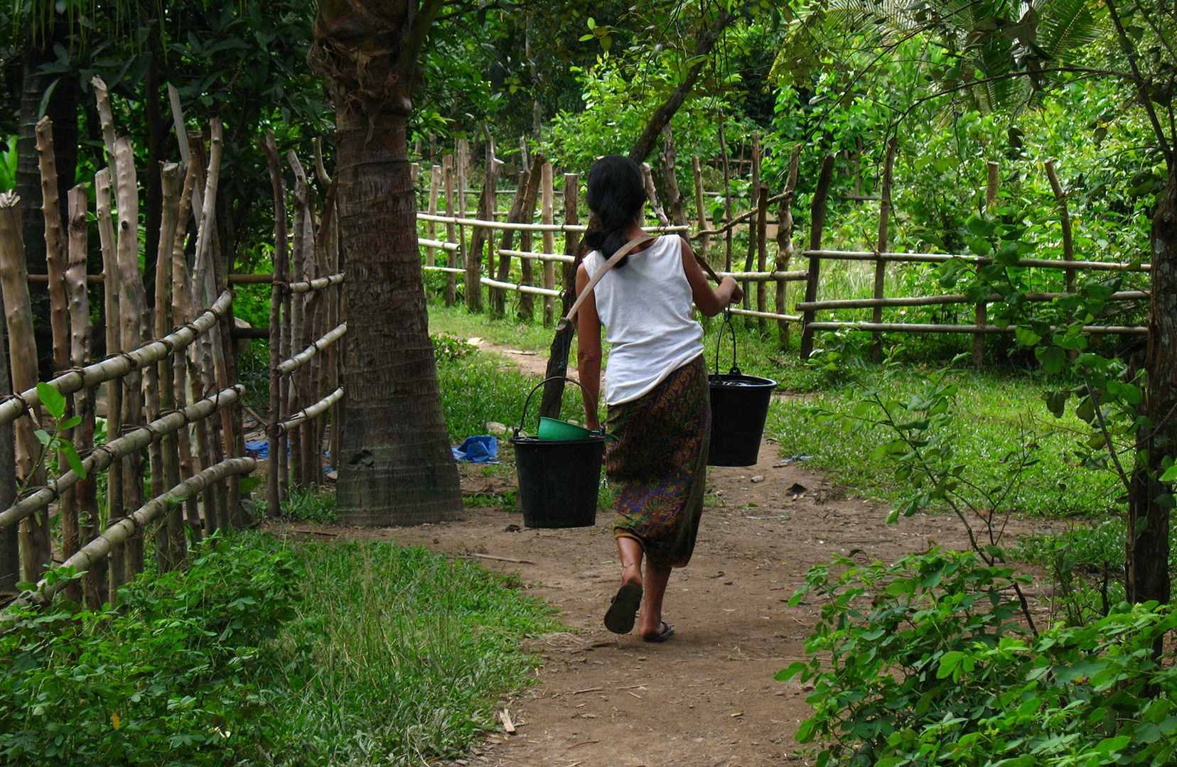 a local women walking with water baskets